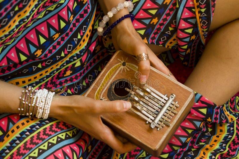 Kalimba da terra arrendada da mulher em no suas mãos e jogo imagens de stock