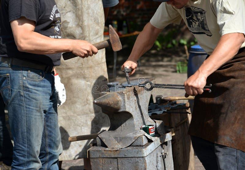 Kaliningrad, Ρωσία Δύο smiths σφυρηλατούν ένα μέταλλο στοκ εικόνα με δικαίωμα ελεύθερης χρήσης