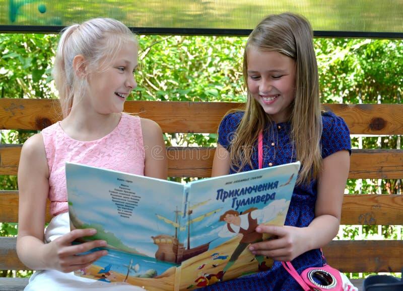Kaliningrad, Ρωσία Οι εύθυμες φίλες κοριτσιών συζητούν το βιβλίο σε έναν πάγκο Το ρωσικό κείμενο - Gulliver ` s ταξιδεύει στοκ φωτογραφίες