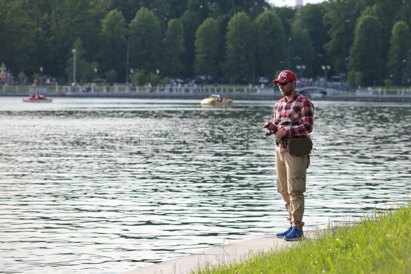 Kaliningrad, Rússia - 1º de junho de 2019: Pesca do homem no lago do parque da cidade imagem de stock