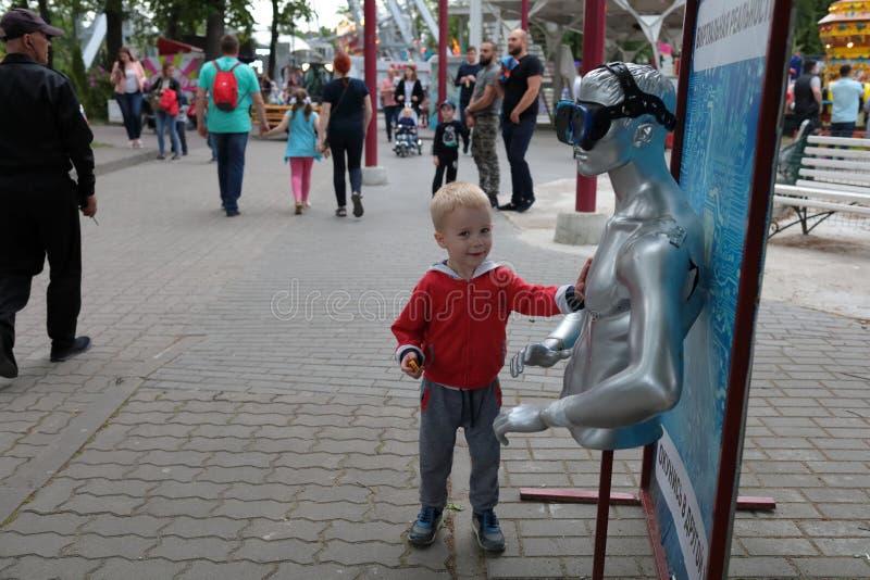 Kaliningrad, Rússia - 1º de junho de 2019: Rapaz pequeno que toca no manequim no parque da cidade imagem de stock royalty free
