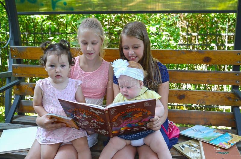 Kaliningrad, Rússia As estudantes das meninas com irmãs mais nova consideram o livro em um banco no parque foto de stock royalty free