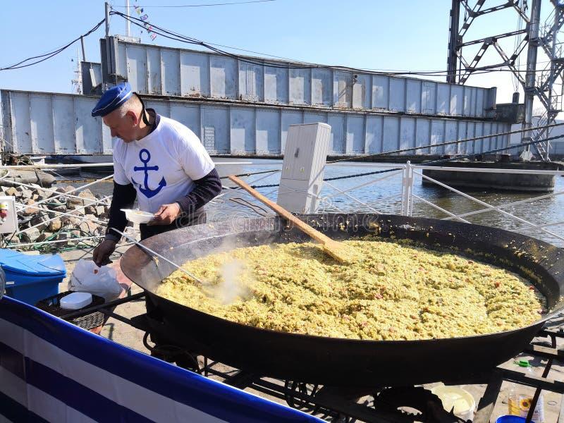 Kaliningrad, Rússia - 13 de abril de 2019: Homem que cozinha o paella no feriado grande do frigideira do dia dos arenques fotografia de stock royalty free
