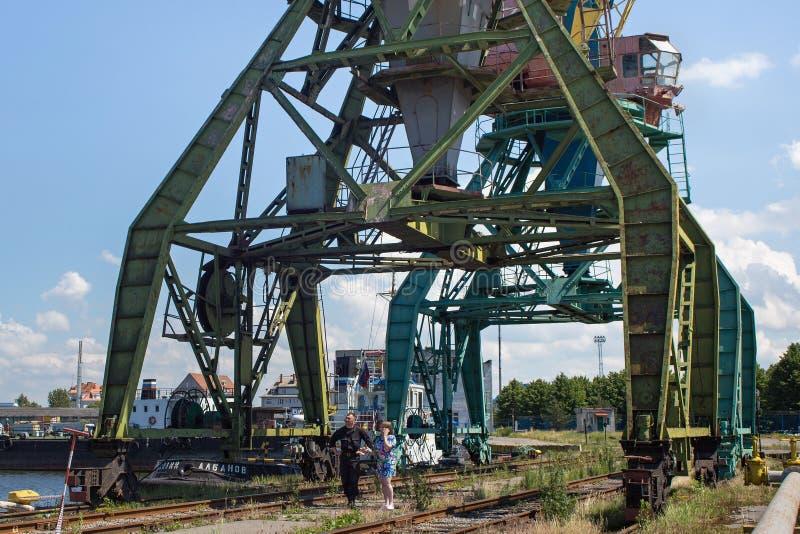 KALININGRAD, RÚSSIA - 19 DE JUNHO DE 2016: Guindastes de patíbulo pesados do porto no porto de pesca do mar de Kaliningrad fotografia de stock royalty free