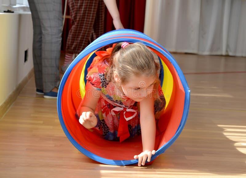 Kaliningrad, Rússia A menina rasteja em um túnel do jogo Um feriado no jardim de infância imagem de stock royalty free