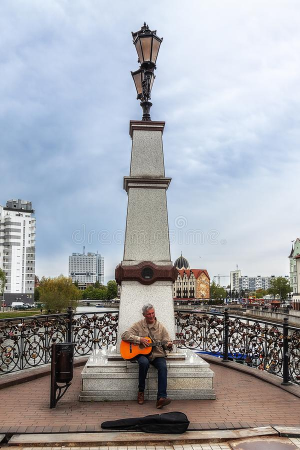Kaliningrad Rússia 05 01 O músico 2019 da rua joga a guitarra perto do monumento foto de stock