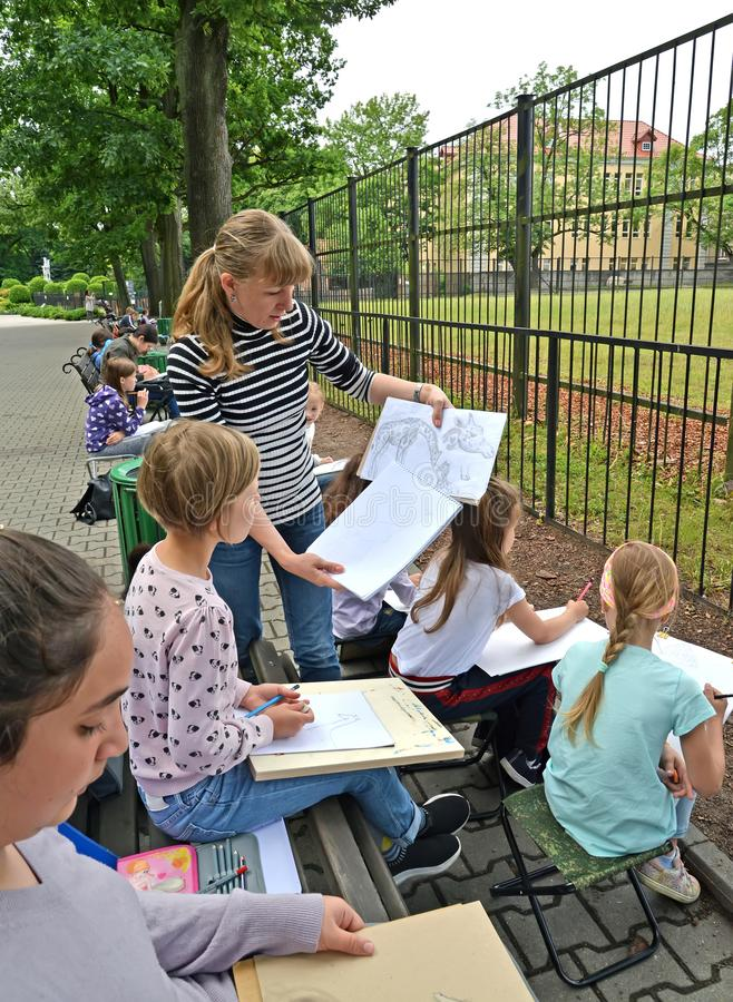 Kaliningrad, Rússia O professor ensina crianças tirar um girafa Um ` s das crianças ao ar livre em um jardim zoológico foto de stock