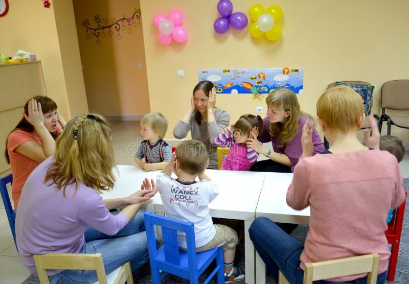 Kaliningrad, Rússia O tutor dá classes do jogo com as crianças e os pais, sentando-se em uma tabela Estúdio do desenvolvimento cr imagens de stock royalty free
