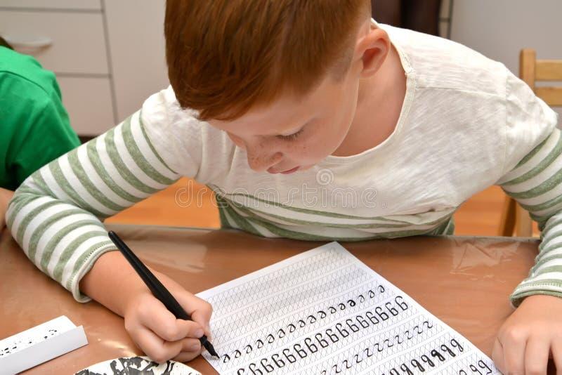Kaliningrad, Rosja Chłopiec pisze listach z calligraphical handwriting obraz stock