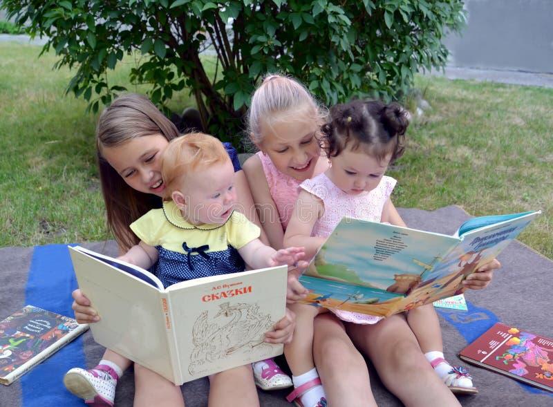 Kaliningrad, Rosja Dzieci różny wiek z interesem rozważają książki, siedzi na trawie w ogródzie zdjęcia stock