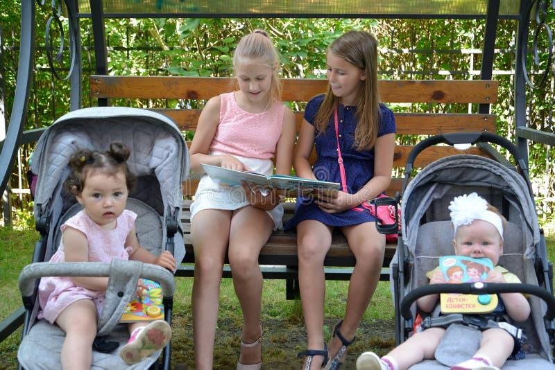 Kaliningrad, Rusland De meisjesmeisjes met enthousiasme bespreken het boek op een bank in het park stock fotografie