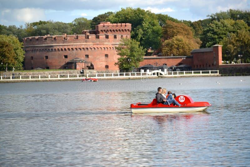 Kaliningrad, Rusland De watergang op een catamaran op het Hoogste meer met een toren van ` Der trekt ` aan - het museum aan wal v royalty-vrije stock afbeeldingen