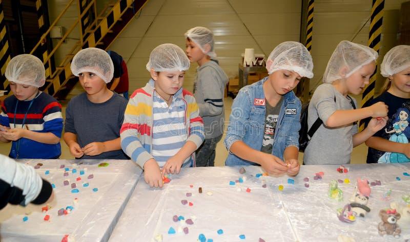 KALININGRAD, RUSLAND Schoolchildren sculpt getallen van mastiek snoepgoed Kinderen in de chocoladefabriek stock foto
