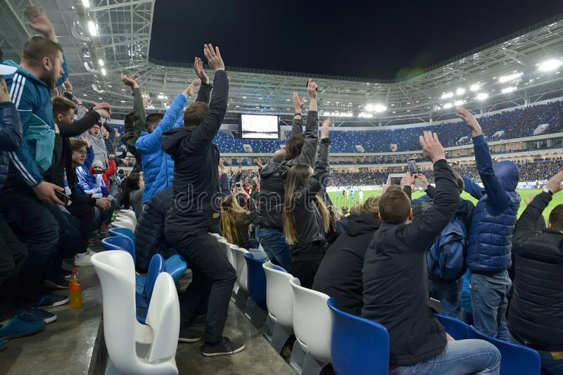 KALININGRAD, RUSSIA. The audience of a football match with the hands which are thrown up for joy. Baltic Arena stadium royalty free stock image