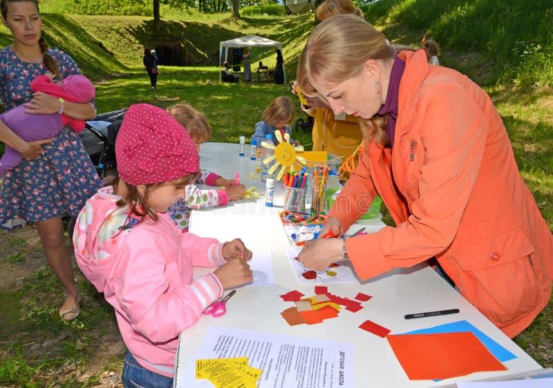 Kaliningrad, Russia L'insegnante mostra alla produzione di applique del bambino Classe del padrone del ` s dei bambini all'aperto fotografia stock
