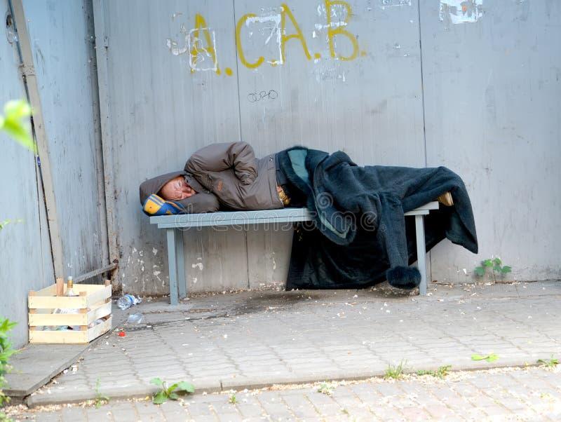 KALININGRAD, RUSSIA. Drunk elderly man sleeps on bench in stop pavilion royalty free stock photo