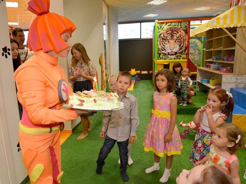 KALININGRAD, RUSSIA - SEPTEMBER 18, 2016: The animator holds festive cake on children's birthday.  royalty free stock photos