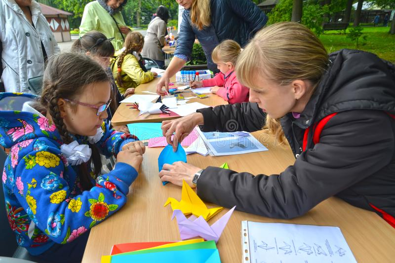 KALININGRAD, RUSSIA. The young woman teaches the girl to put origami. Children`s master class in the open air stock photo