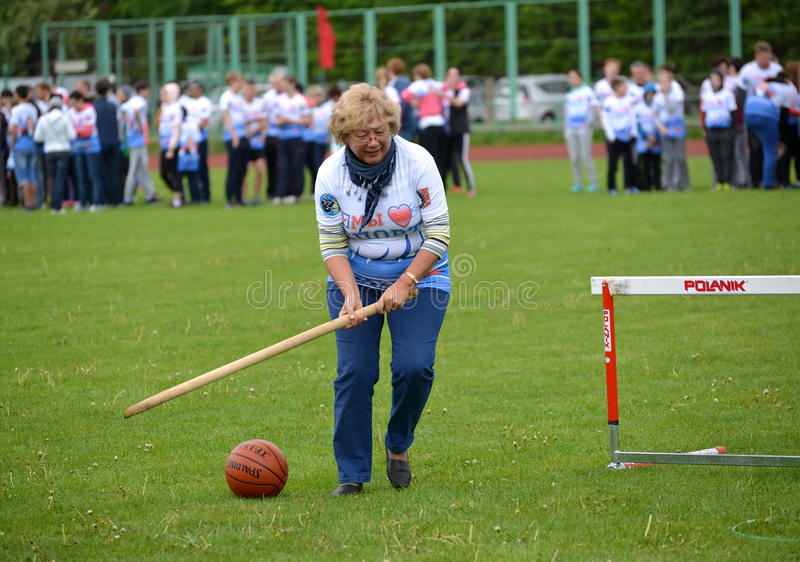 KALININGRAD, RUSSIA. The woman of average years rolls before herself a ball by means of a stick at the competitions Cheerful stock image