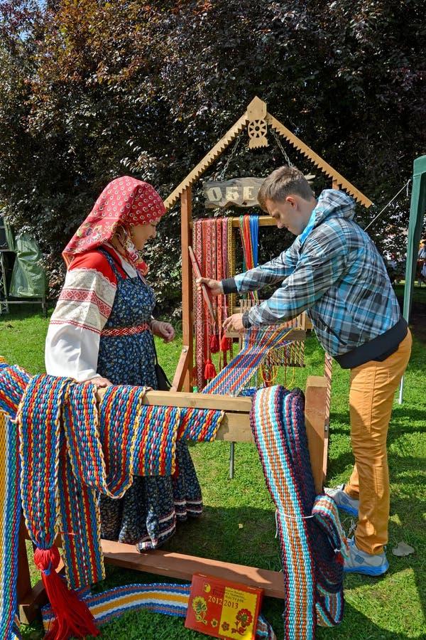 KALININGRAD, RUSSIE - 15 AOÛT 2014 : Le tisserand enseigne le jeune homme à tisser avec le roseau d'aide images stock