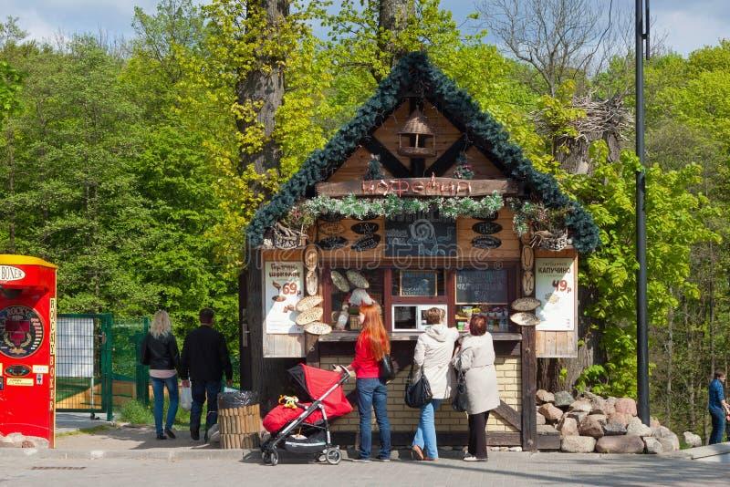 KALININGRAD, RUSSIE - 27 AVRIL 2014 : Les personnes inconnues font la queue pour le café près du petit magasin en bois photos libres de droits