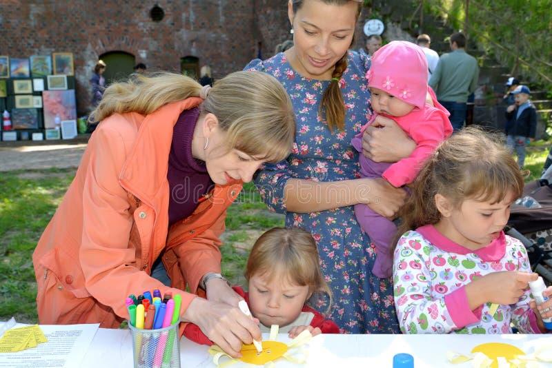 Kaliningrad, Russie Le professeur enseigne l'enfant à faire l'applique en plein air images stock