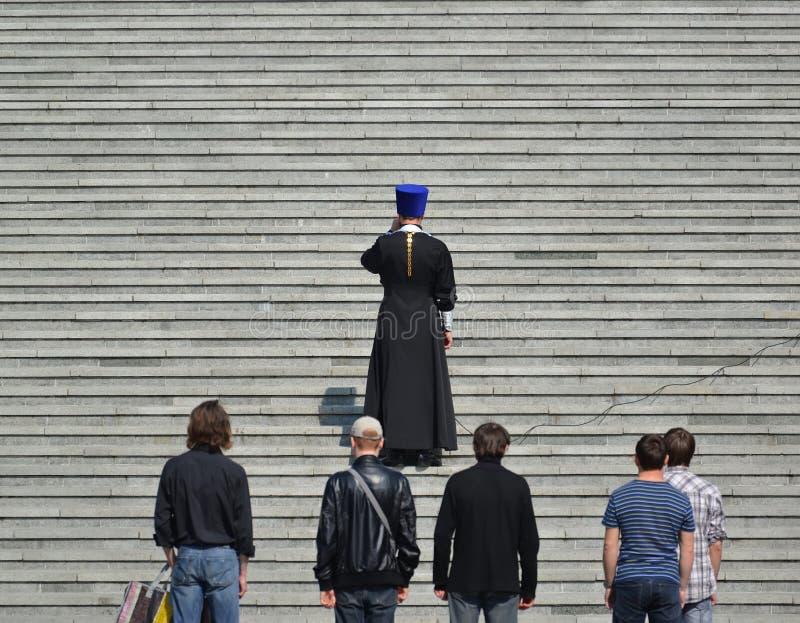 Kaliningrad, Russland Der orthodoxe Priester sagt ein Gebet an den Schritten der Kathedrale von Christus der Retter in Kaliningra lizenzfreies stockfoto