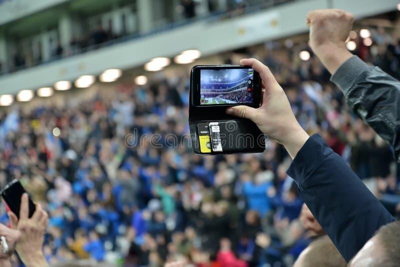 Kaliningrad, Russland Die Fan ` s Hand mit dem Smartphone an einem Fußballspiel Baltisches Arena-Stadion stockbild
