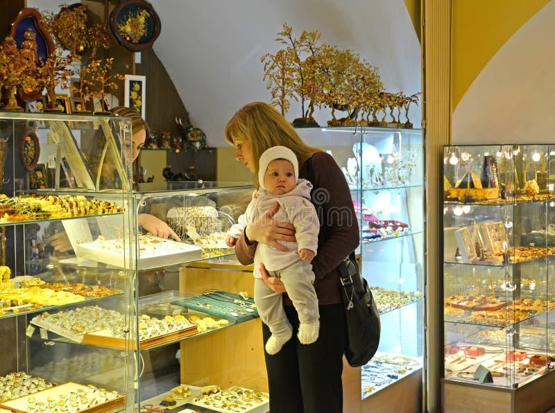 Kaliningrad, Russland Die Frau mit dem chilld wählt bernsteinfarbigen Schmuck im Shop des Museums des Bernsteines stockbilder