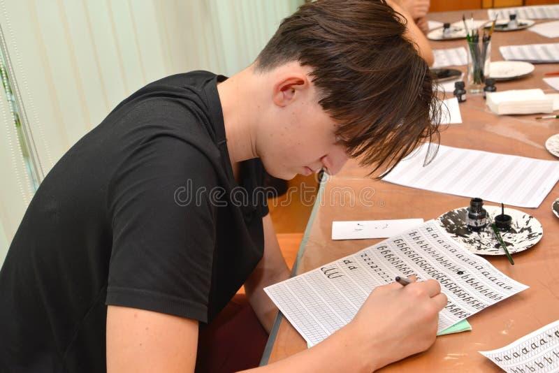 Kaliningrad Ryssland Den unga mannen kopplas in i en kalligrafi i studio royaltyfri fotografi