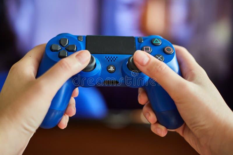 KALININGRAD RYSSLAND - JULI 26, 2019: Unga flickan rymmer en fjärrkontroll från en modig konsol En flicka spelar videospel arkivbilder