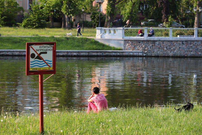 Kaliningrad Ryssland - Juni 01, 2019: Kvinna som sitter på kusten av stadssjön arkivfoto
