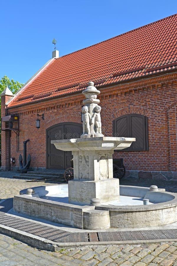 Kaliningrad Ryssland Parkera den Puttenbrunen springbrunnen Putti mot bakgrunden av tegelstenbyggnaden av ett lager royaltyfria bilder