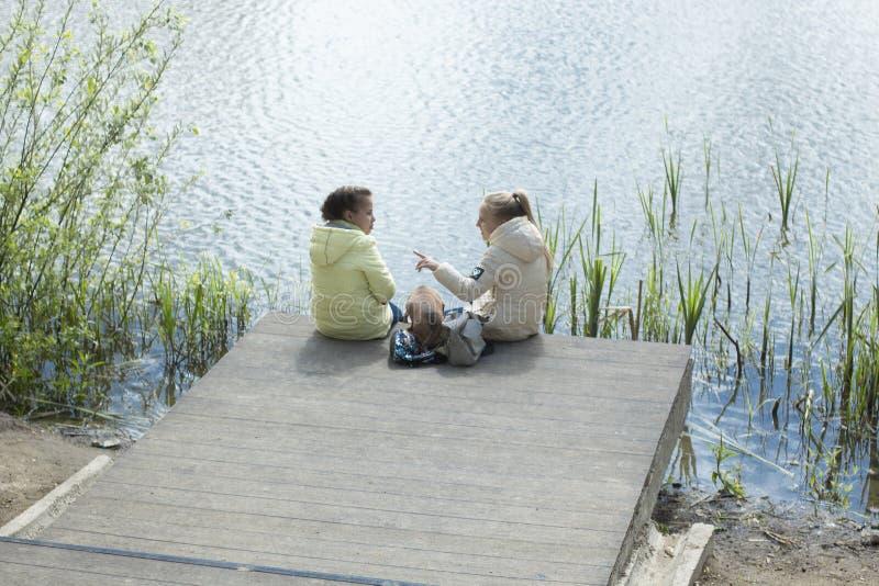 Kaliningrado 2019 dos chicas j?venes que se sientan en el lago imágenes de archivo libres de regalías