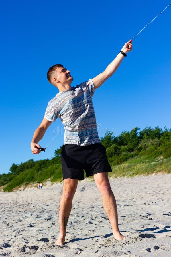 Kaliningrado, Rusia - 23 de junio de 2019: Hombre que sostiene una cometa en la playa del mar Báltico en día de verano Ci?rrese e foto de archivo libre de regalías