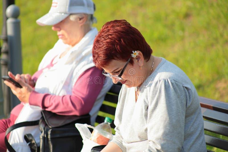 Kaliningrado, Rusia - 1 de junio de 2019: Libro de lectura de la mujer en el parque de la ciudad fotos de archivo