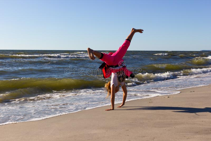 Kaliningrado, Rusia - 23 de junio de 2019: Niña que hace el cartwheel en la playa del mar Báltico en día de verano imagenes de archivo