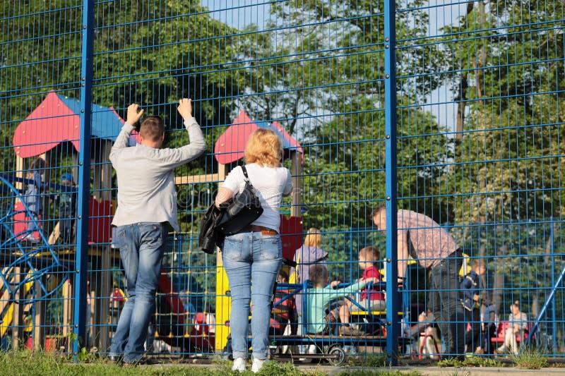 Kaliningrado, Rusia - 1 de junio de 2019: Padres que miran a niños el jugar en parque de la ciudad fotografía de archivo libre de regalías