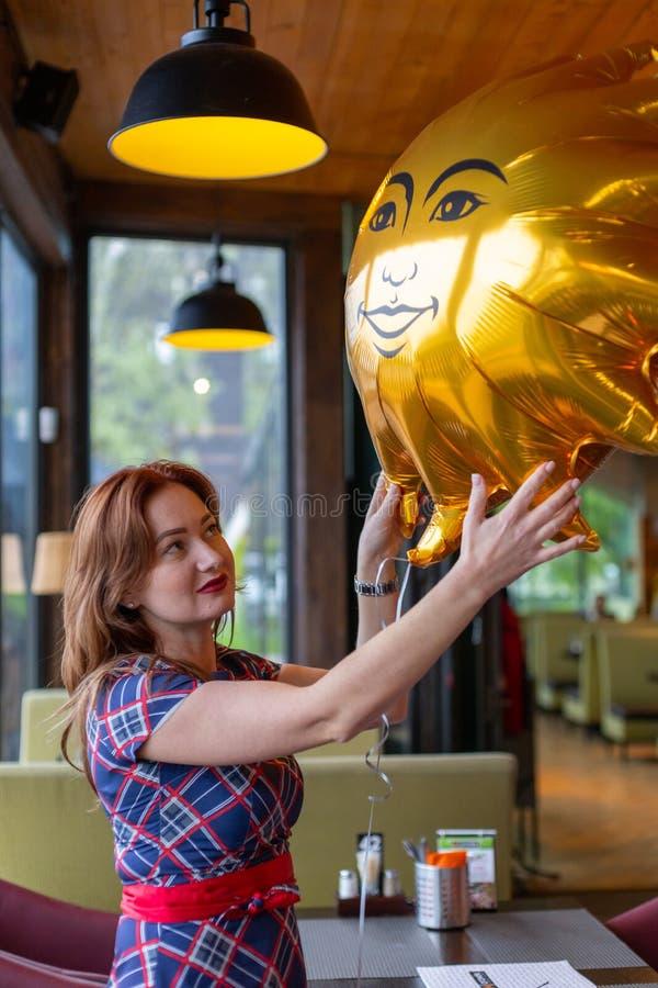 Kaliningrado, Rusia - 13 de mayo de 2019: La muchacha hermosa toma un globo del regalo en su día del aniversario en el restaurant imagen de archivo