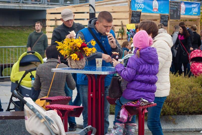 KALININGRADO, RUSIA - 9 DE SEPTIEMBRE DE 2014: Familia desconocida que tiene almorzar cerca del café de la comida de la calle en  fotografía de archivo