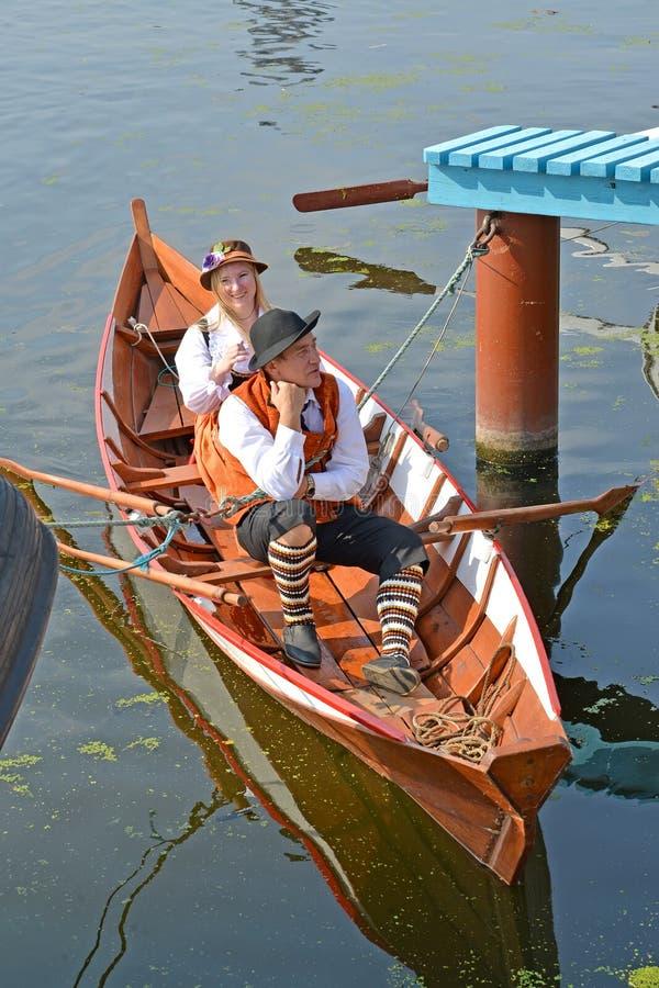 Kaliningrado, Rusia El hombre y la mujer en trajes nacionales sientan los flotadores en el barco Asamblea del agua del día de fie fotos de archivo