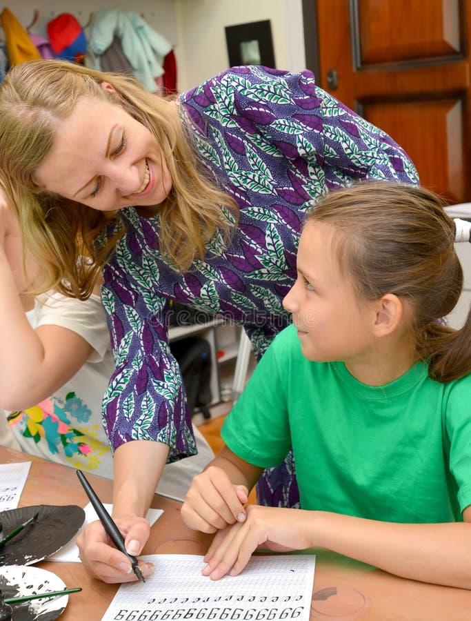 Kaliningrado, Rusia El profesor alegre y la colegiala en el empleo una caligrafía en el estudio de los niños fotos de archivo