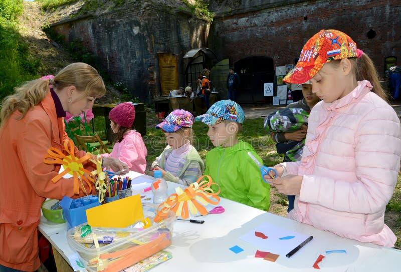 Kaliningrado, Rusia El profesor enseña a niños a hacer applique del volumen Clase del amo del ` s de los niños en el aire abierto fotografía de archivo libre de regalías