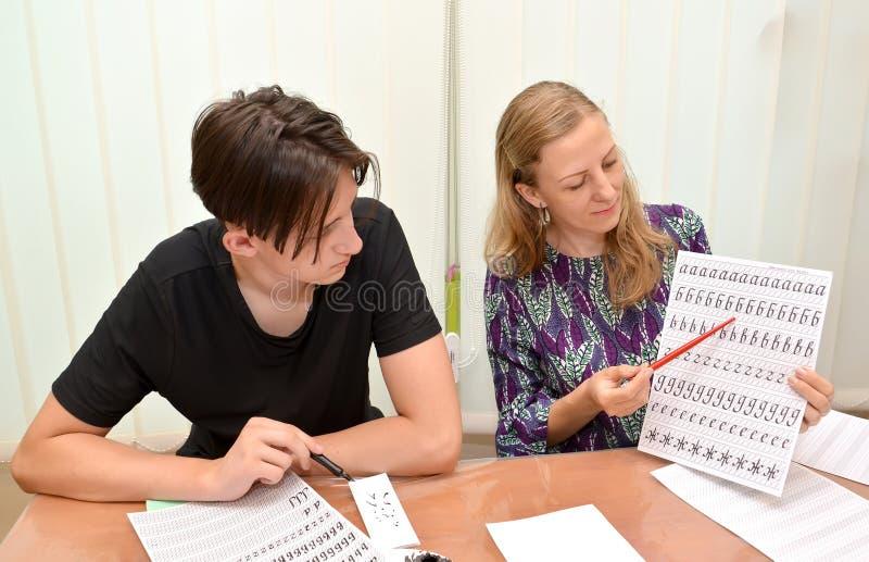 Kaliningrado, Rusia El profesor muestra a la escritura del adolescente de letras Empleo una caligrafía en el centro que se convie fotografía de archivo