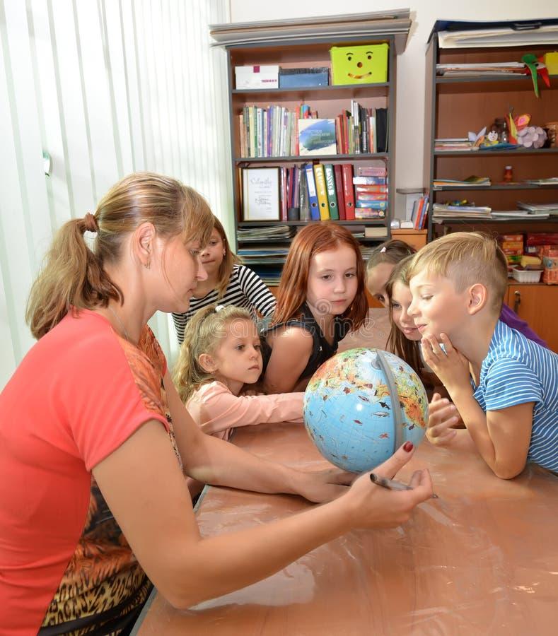 Kaliningrado, Rusia El profesor muestra a los niños el globo Empleo en el centro que se convierte de los niños foto de archivo