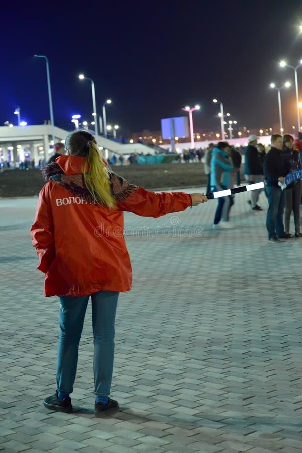 Kaliningrado, Rusia El voluntario con un personal en una mano muestra una manera del estadio imagen de archivo
