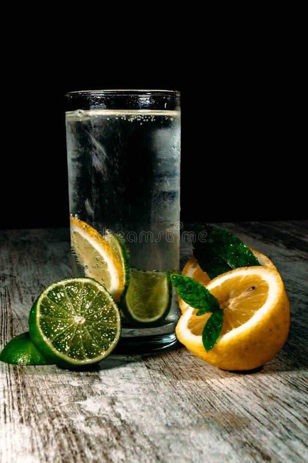 Kalk en citroenplons met ijs en wat detoxwater stock foto