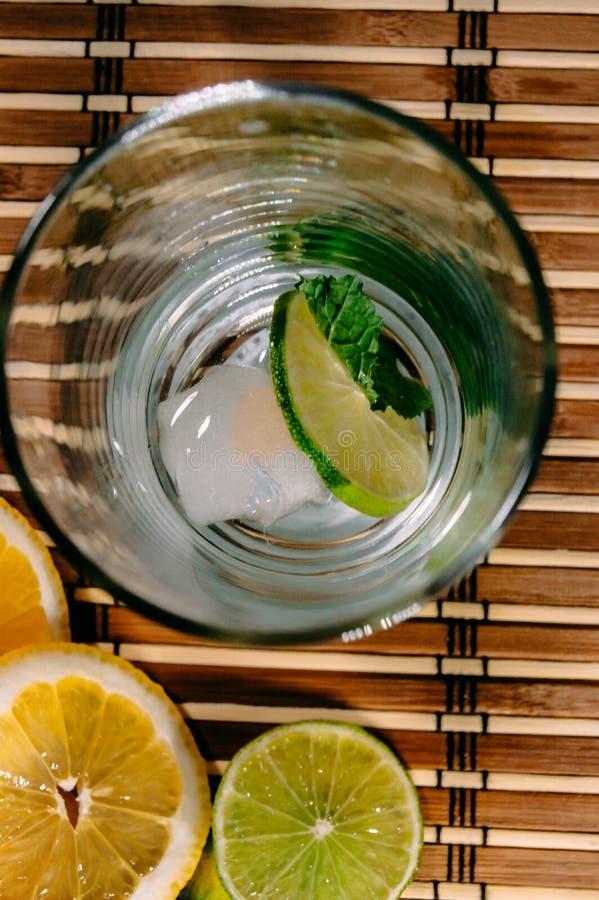 Kalk en citroenplons met ijs en wat detoxwater royalty-vrije stock afbeeldingen