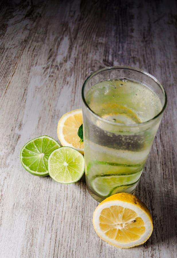 Kalk en citroenplons met ijs en wat detoxwater royalty-vrije stock fotografie