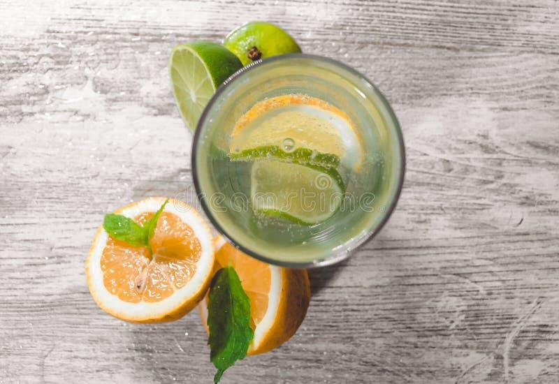 Kalk en citroenplons met ijs en wat detoxwater stock foto's